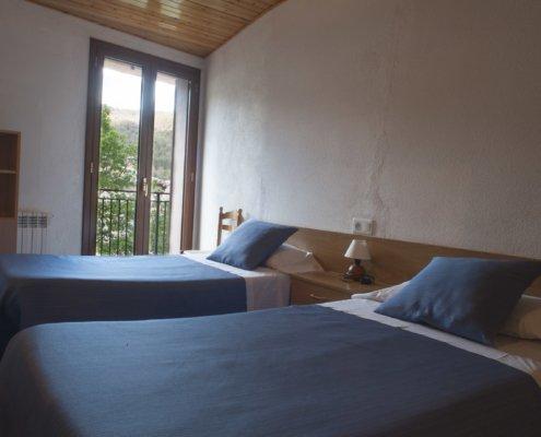 Habitació amb llits individuals i televisió